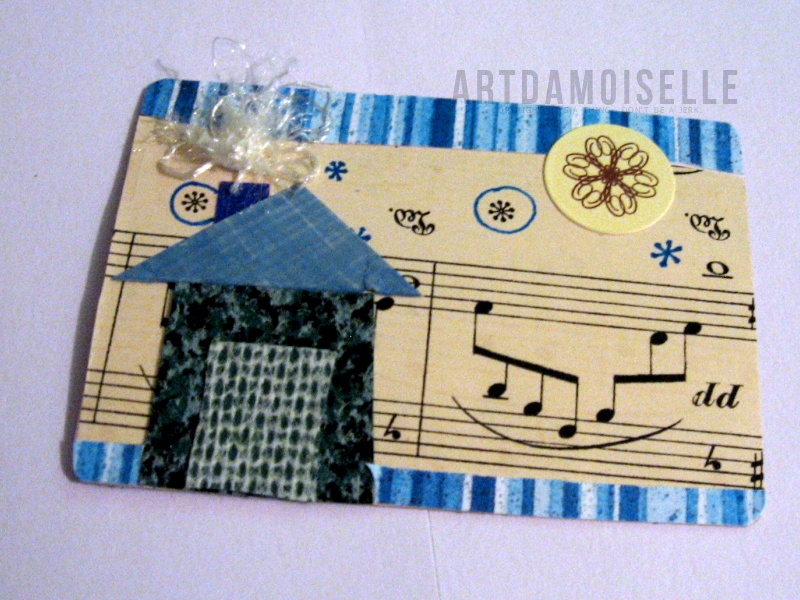 A card with a background of sheet music and a collaged house with blue borders.