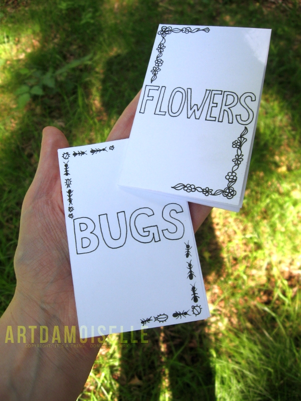 "A hand holding two small handmade booklets titled ""FLOWERS"" and ""BUGS""."