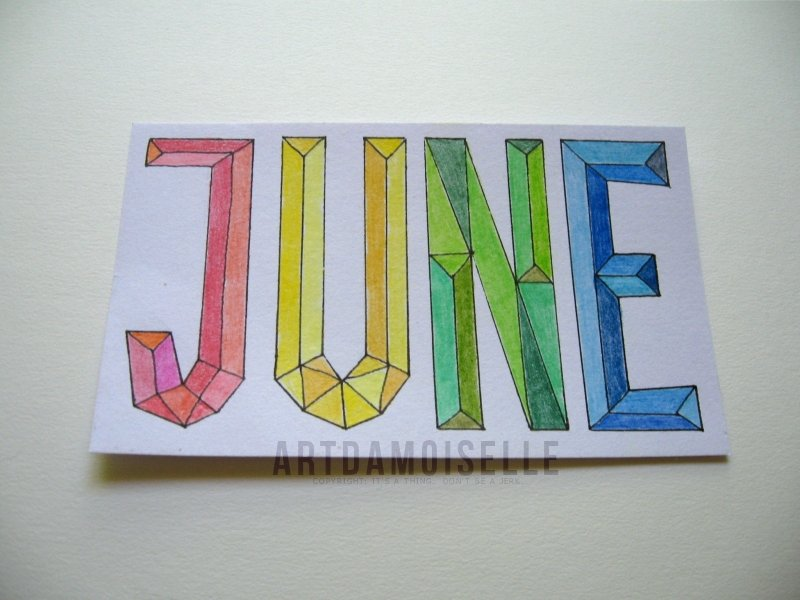 "An unlined index card with large faceted block letters in primary colors, reading ""JUNE""."